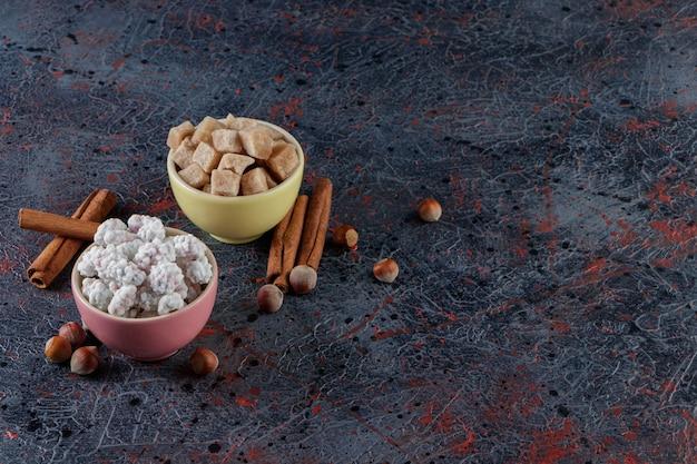 건강한 견과류와 계피 스틱과 함께 달콤한 흰색과 갈색 사탕으로 가득한 두 개의 다채로운 그릇.