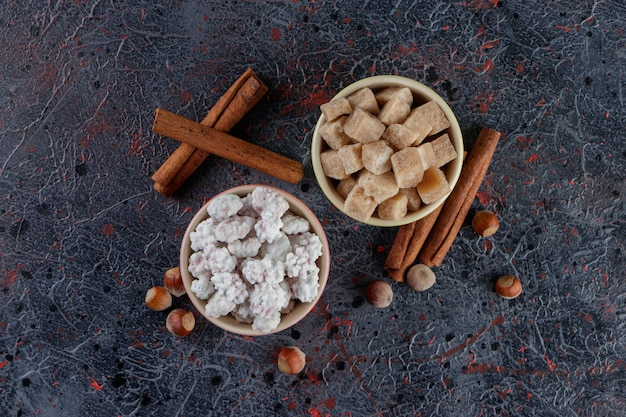 Two colorful bowls full of sweet white and brown candies with healthy nuts and cinnamon sticks
