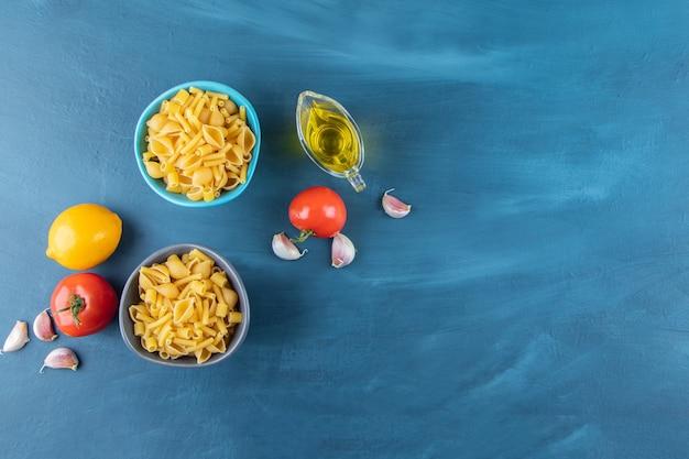 Две красочные миски сырых макарон со свежими красными помидорами и одним целым лимоном.