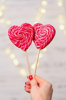 Two colorful candy in the shape of hearts on the background bokeh, close-up. the concept of valentine's day.