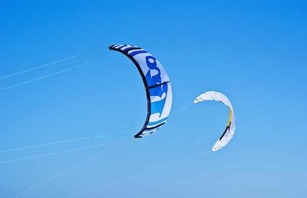 Two colorful kites of kiteboarding is flying in the blue sky