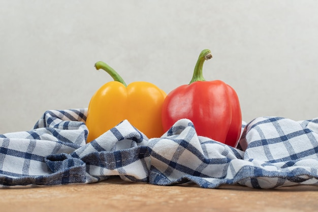 Два красочных перца, лежащих на скатерти