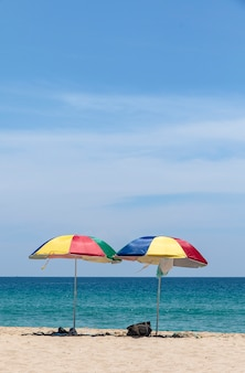Two colorful umbrellas on white sand beach.