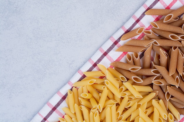 Two colors of raw pasta on striped tablecloth