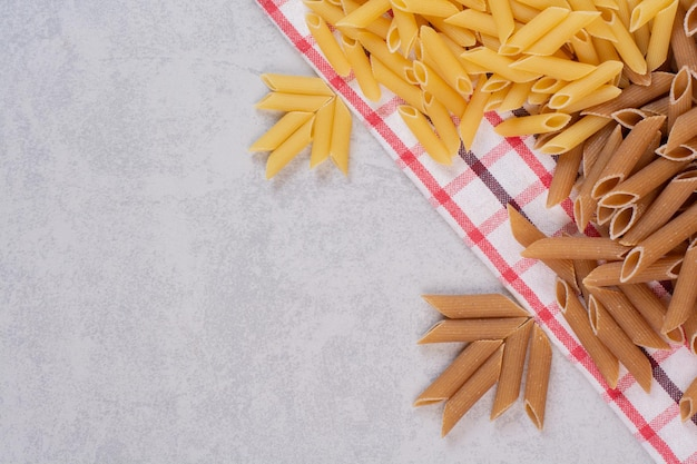 Two colors of raw pasta on striped tablecloth.