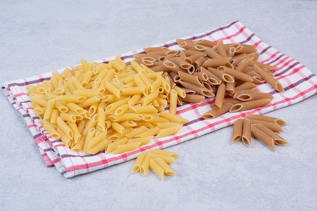 Two colors of raw penne pasta on striped tablecloth