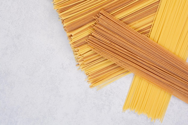 Two colors of raw spaghetti pasta on white table.