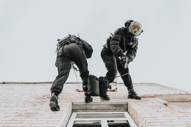 На базе тренируются два спецназовца. альпинисты. swat, полиция, концепция борьбы с терроризмом. смешанная техника