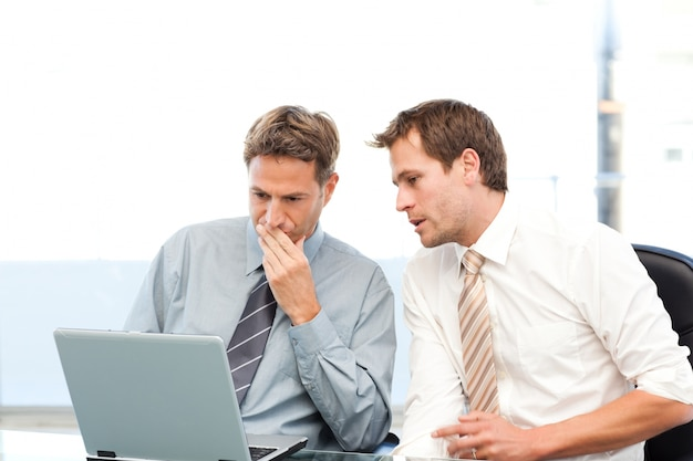 Two concentrated businessmen working together on a laptop