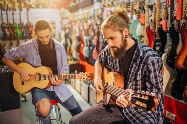 Два концентрированных молодой человек играет на акустической гитаре. они сидят на табуретках в комнате, полной электрогитар. бородатые парни играют вместе.