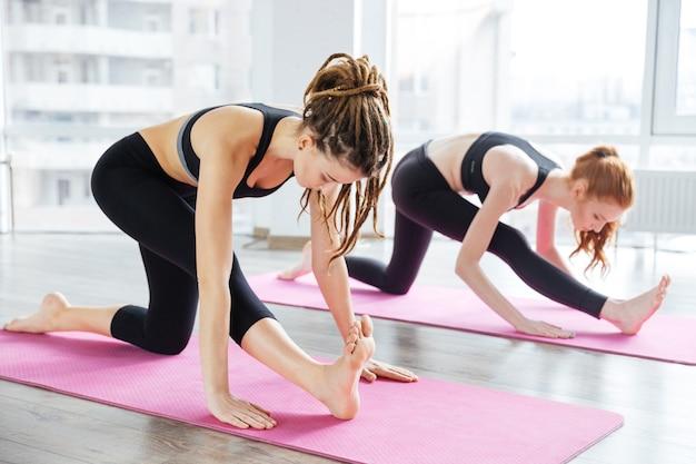 Две сосредоточенные молодые женщины растягиваются и практикуют йогу в студии