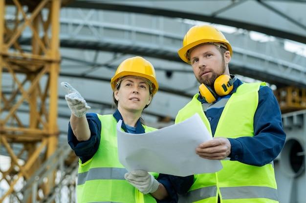 Два уверенных строителя с планом обсуждают строительную площадку