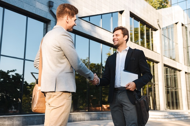 Two confident businessmen standing outdoors, shaking hands