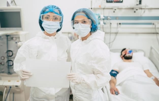 Два уверенных в себе врача в защитных костюмах стоят на фоне пациента с коронавирусом