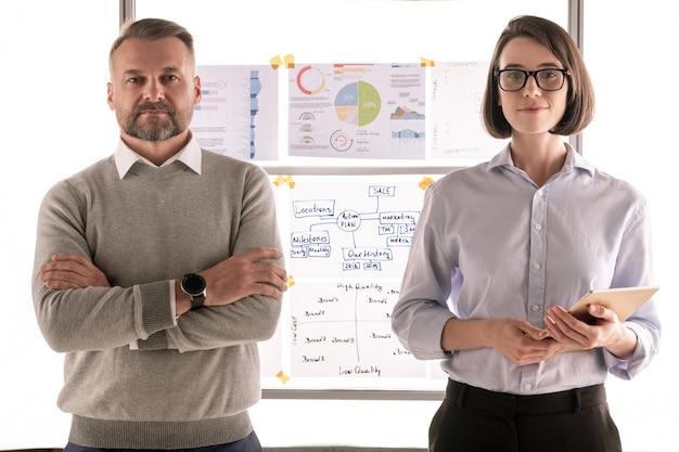 Два уверенных в себе финансиста в формальной одежде смотрят на вас, стоя на доске