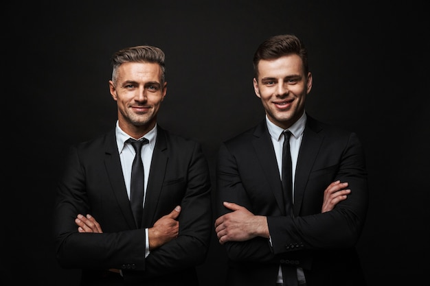 Two confident handsome businessmen wearing suit standing isolated over black wall, arms folded