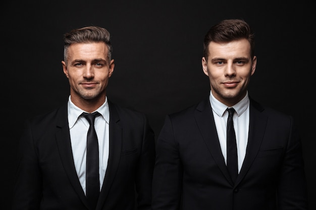 Two confident handsome businessmen wearing suit standing isolated over black wall, looking at camera