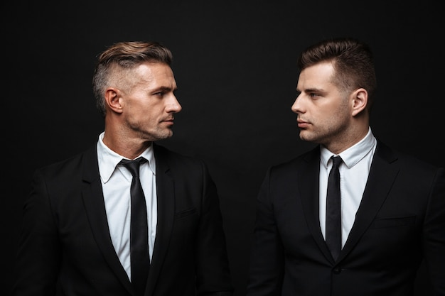 Two confident handsome businessmen wearing suit standing isolated over black wall, looking at each other