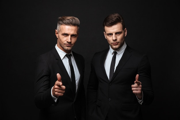 Two confident handsome businessmen wearing suit standing isolated over black wall, pointing at camera
