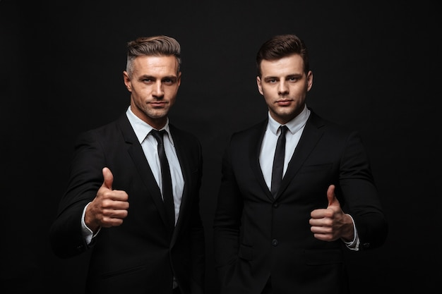 Two confident handsome businessmen wearing suit standing isolated over black wall, thumbs up