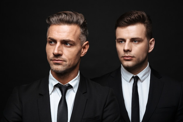 Two confident handsome businessmen wearing suit standing isolated over black wall