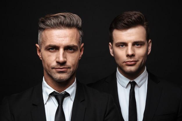 Два уверенных в себе красивых бизнесмена в костюме, стоящие изолированно над черной стеной и смотрящие в камеру