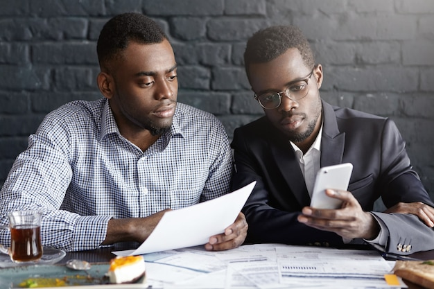 Two confident and serious african-american businessmen focused on paperwork