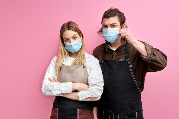Two confident waiters of restaurant stand together dressed in medical mask during quarantine