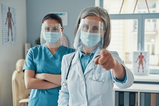 Две уверенные в себе женщины-коллеги в медицинской форме и защитной спецодежде жестикулируют и смотрят в камеру во время работы в больнице