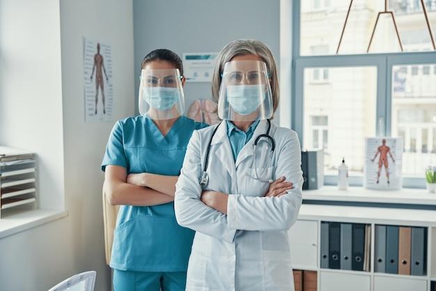 Две уверенные в себе женщины-коллеги в медицинской форме и защитной спецодежде, скрестив руки на груди, смотрят в камеру во время работы в больнице