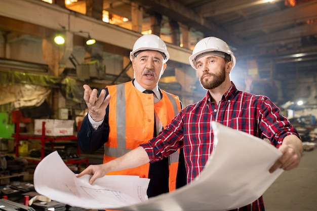 Two confident workers in uniform and hardhats discussing technical details or new industrial machine equipment