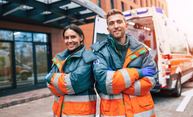 Two confident young doctors  on ambulance and hospital