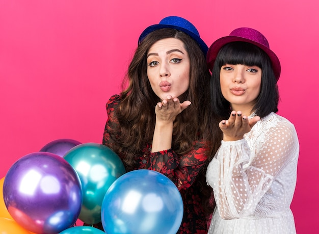 Two confident young party womans wearing party hat standing behind balloons both looking at front sending blow kiss isolated on pink wall