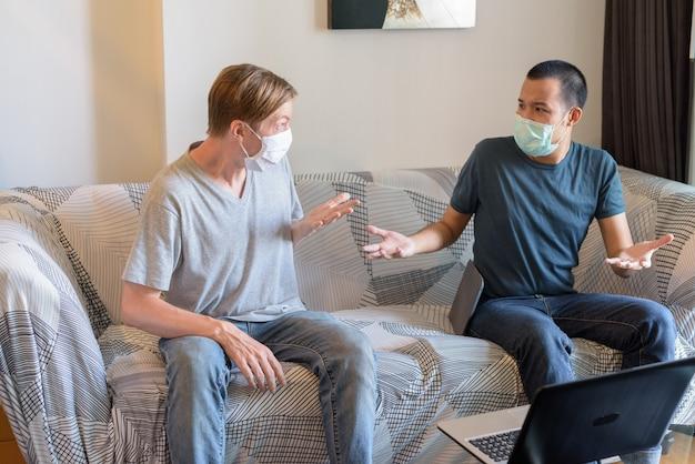 友人が自宅で検疫下で肩をすくめてマスクを持つ2つの混乱した多民族男性