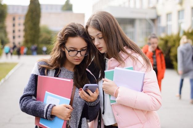 Два сбитых с толку студента читают плохие новости по телефону