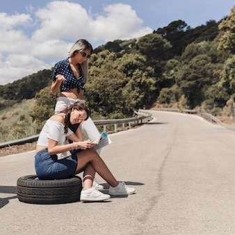 Two confused young woman looking at map on road