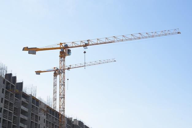 Два строительных крана на фоне ясного голубого неба. фасад здания в углу каркаса. строительная площадка.