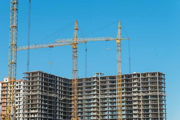 未完成の建物の近くの2つの建設用クレーン。建設と開発のコンセプト