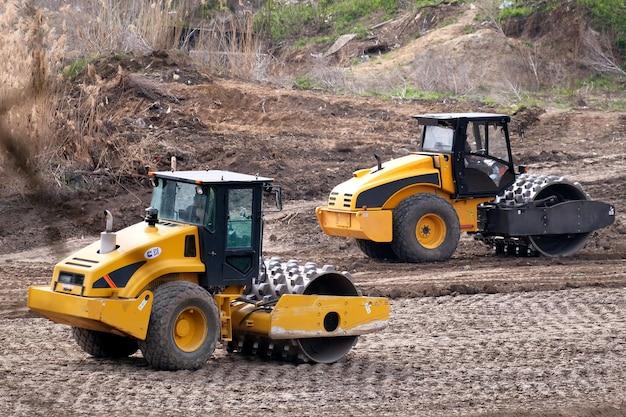 Две строительные тяжелые промышленные машины работают над прокладкой новой дороги