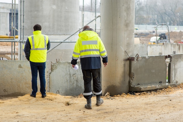 두 명의 건설 관리자가 건설 현장에서 협의합니다.