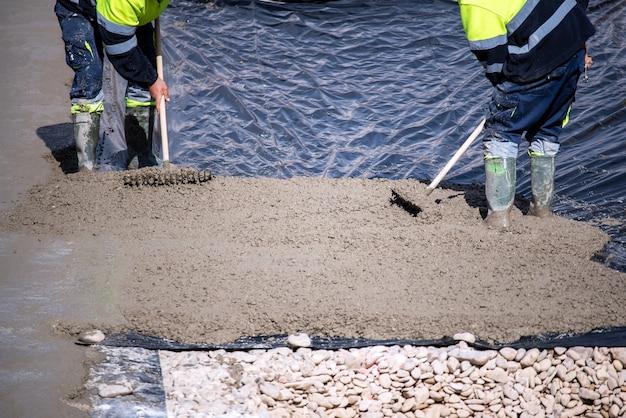 プラスチックシートで床に混合物を注ぐ作業中の2人の建設作業員がクローズアップ
