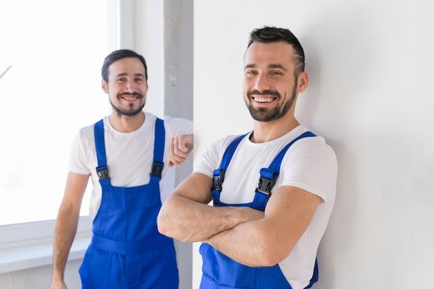 Двое строителей в комбинезоне смотрят в камеру