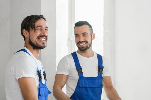 Два строителя в униформе улыбаются
