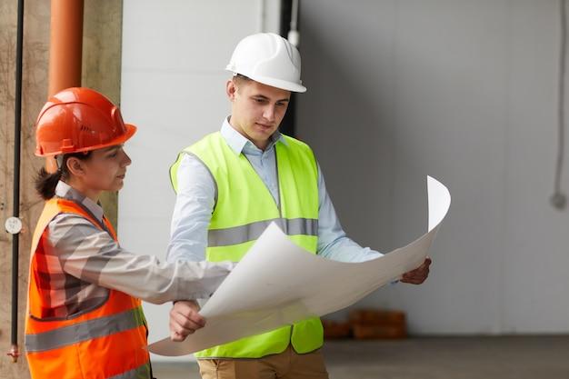 Два строителя в рабочих шлемах вместе изучают план, стоя в пустом здании