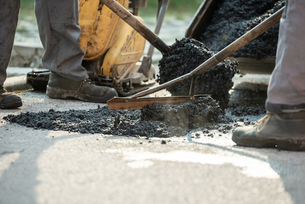 Two construction workers patching bump in the road