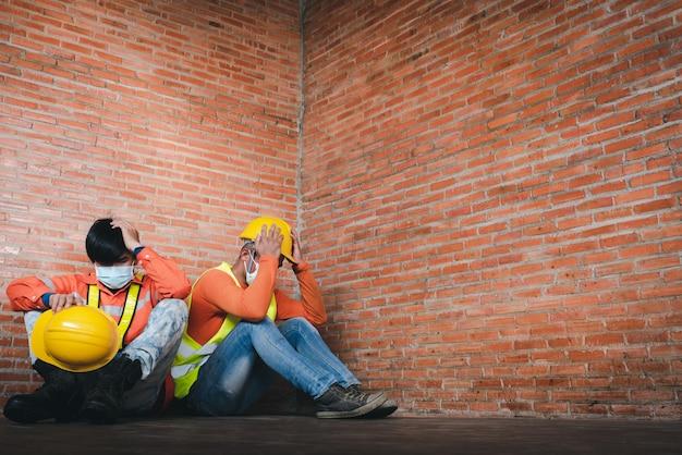 Двое строителей сожалеют о том, что сидят грустно на рабочем месте. ношение медицинской маски для предотвращения covid-19 - это безработица и экономический кризис. безработица не удалась во время covid-19