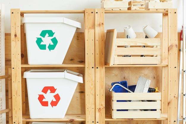 Два контейнера для мусора и деревянные ящики с инструментами на полках