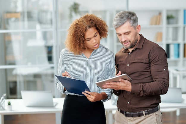 Два современных банкира проверяют финансовые данные на бумаге и в планшете, обсуждая их на встрече в офисе
