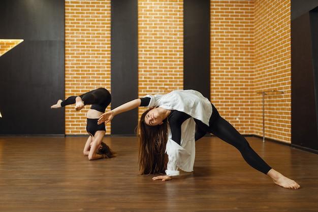 スタジオで2人のコンテンポラリーダンスパフォーマーがポーズをとる。クラスでトレーニングする女性ダンサー、モダンな優雅なダンス、ストレッチ体操