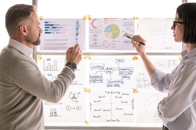 Два современных экономиста стоят у доски в офисе и указывают на финансовые бумаги, обсуждая их
